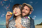 Young couple blowing bubbles on beach, close up