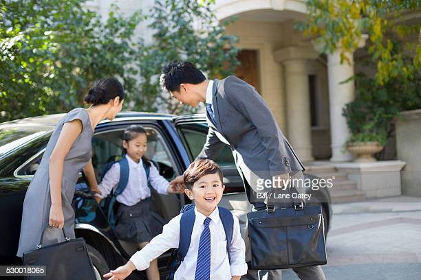 Young couple bringing their children back from school