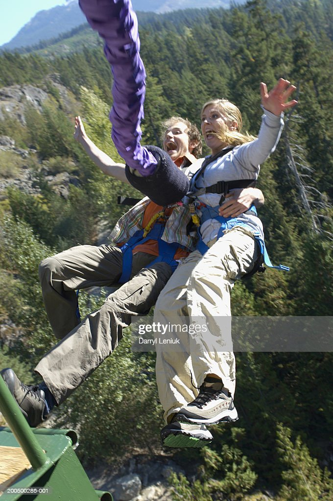 Young couple bungee jumping, screaming : Stock Photo