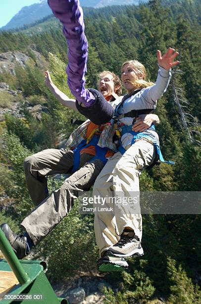 Young couple bungee jumping, screaming