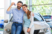 Young couple in the showroom, choosing a car