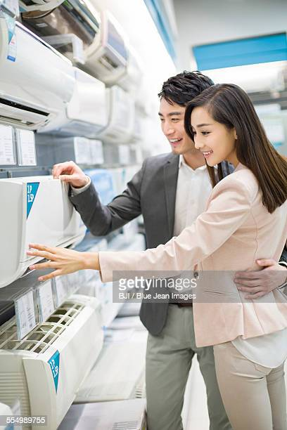Young couple buying air conditioner in electronics store