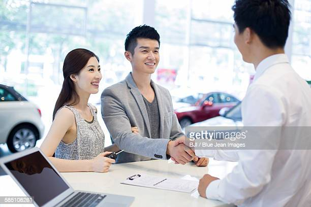 Young couple buying car in showroom