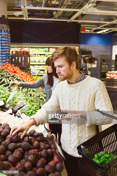 Young couple buying groceries at supermarket
