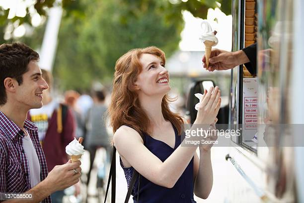 Young couple buying icecreams from a van