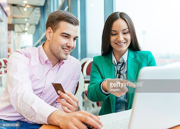 Young couple buying new items on internet auctions and smiling