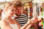 Summer holidays shopping concept. Young couple of tourists buying souvenirs in gift street stall outdoor