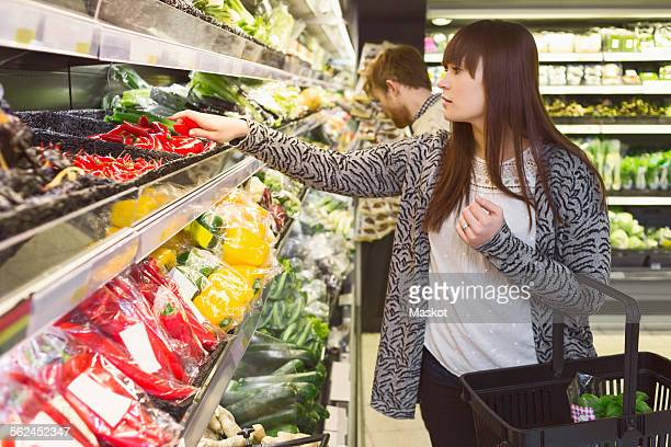 Young couple buying vegetables in supermarket