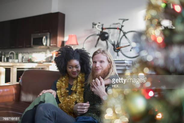 A young couple by a Christmas tree