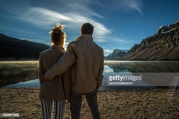 Young couple by the lake watching sunrise