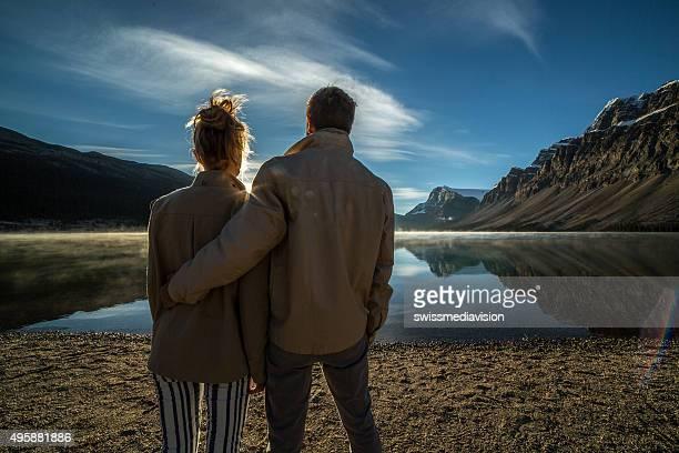Jeune couple en regardant le lever du soleil sur le lac