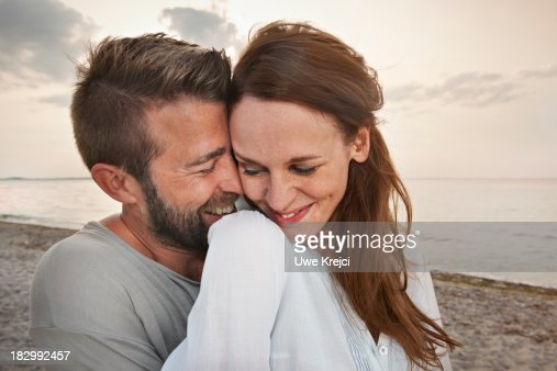 Young couple by the sea, smiling
