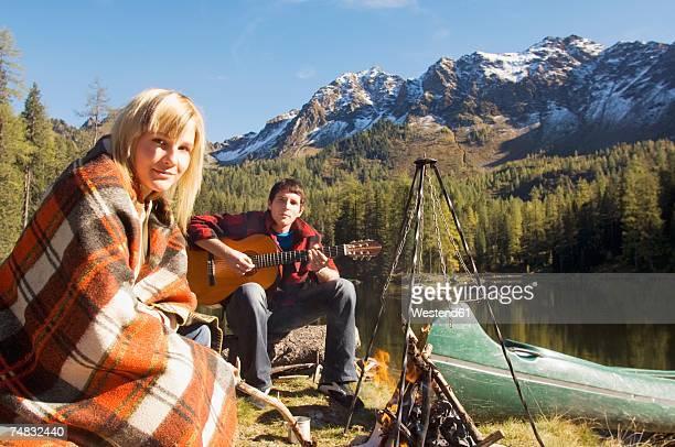 Young couple camping at lake, man playing guitar