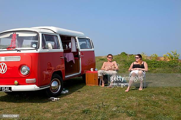A young couple camping in a VW campervan on the clifftops over Mundesley on the Norfolk coast