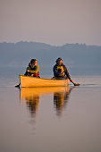 Young couple canoeing in Irondequoit Bay, Rochester, New York, USA.