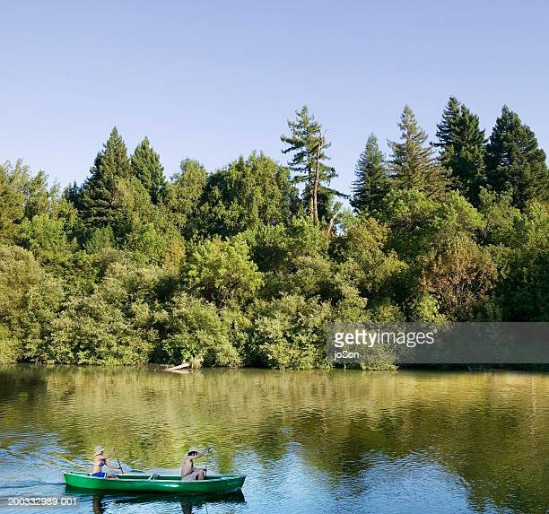 Young couple canoeing, side view, spring