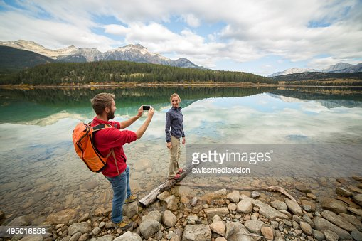 Young couple capturing autumn vacation moments