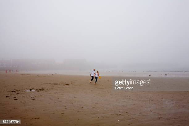 A young couple carrying a yellow bucket between them run towards the sea on a misty Scarborough beach The Scarborough is a town on the North Sea...