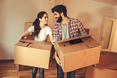 Young couple carrying big cardboard into a new home.Moving house.Real estate concept.