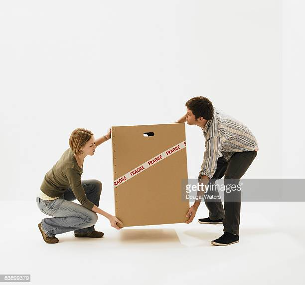 Young couple carrying carboard box.