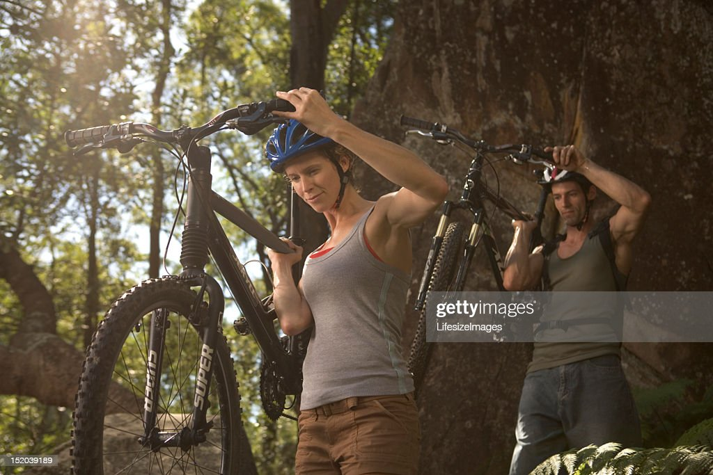 Young couple carrying mountain bikes in forest : Stock Photo