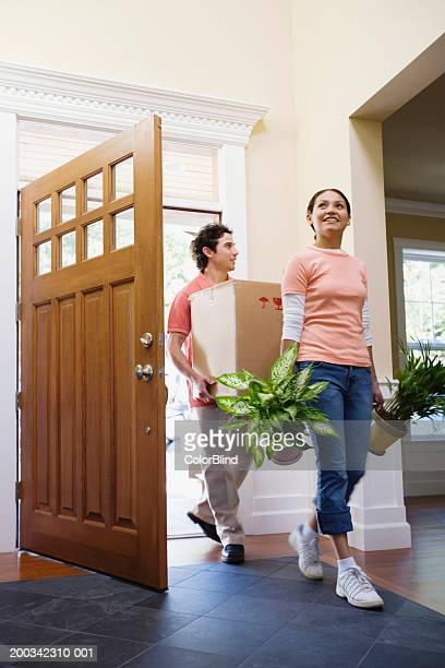 Young couple carrying plants and carton into new home