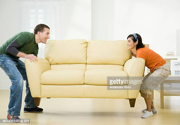 Young couple carrying sofa in new flat, side view