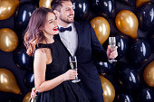 Elegant couple surrounded by black balloons.