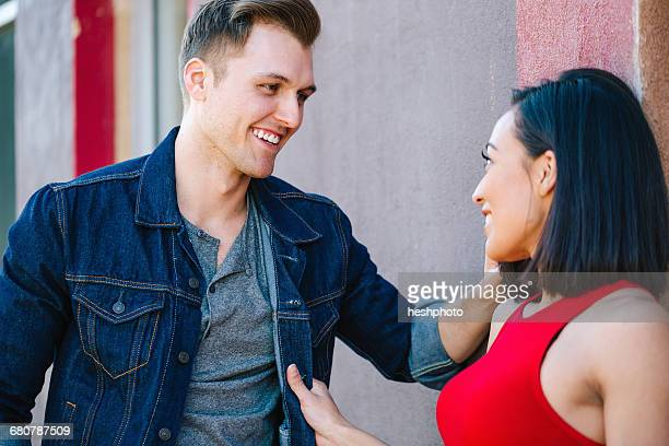 Young couple chatting against wall