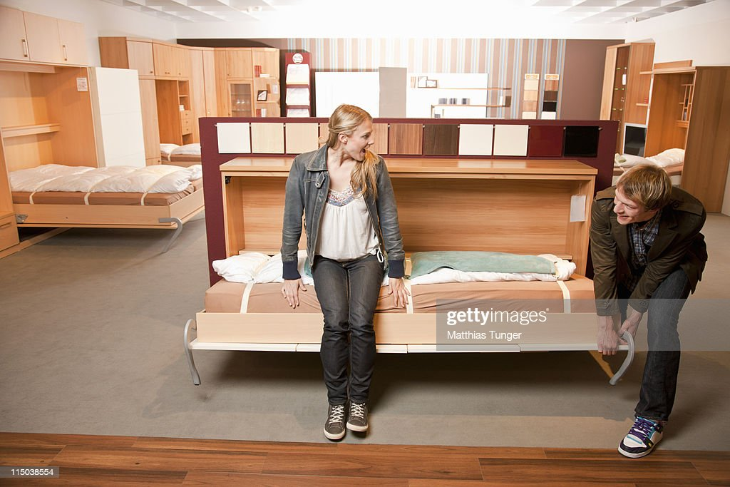 young couple checking functions of foldaway bed stock photo - Fold Away Bed