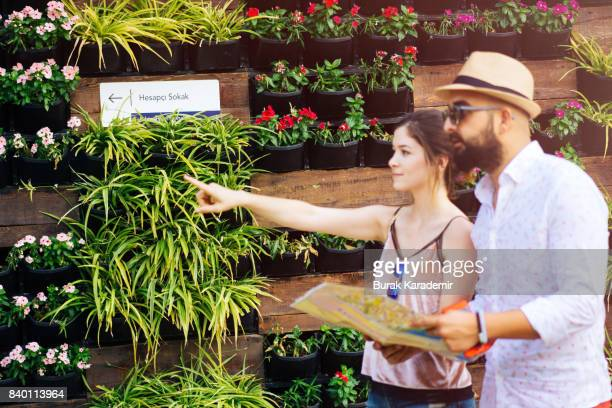 Young couple checking map and pointing somewhere