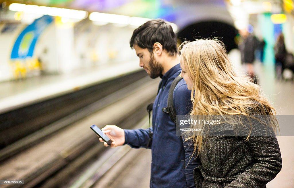Bahnhof Junges Paar, die Ankunftszeit auf Smartphone-App : Stock-Foto