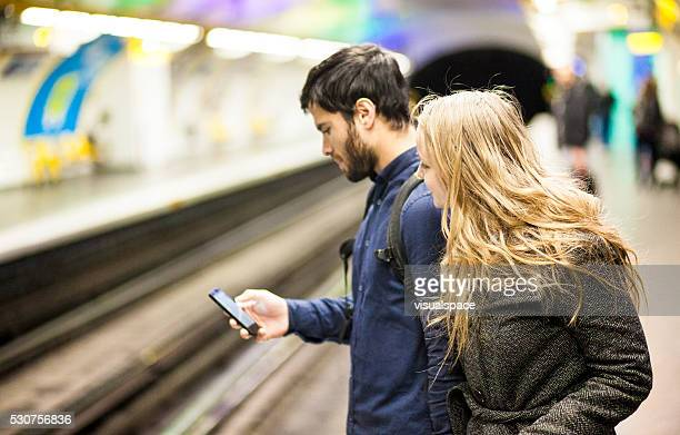 Young Couple Checking Train Arrival Times On Smartphone App