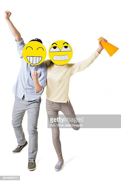 Young couple cheering with two happy emoticon faces in front of their faces