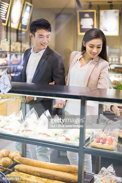 Young couple choosing cakes in bakery