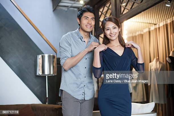 Young couple choosing dress in clothing store