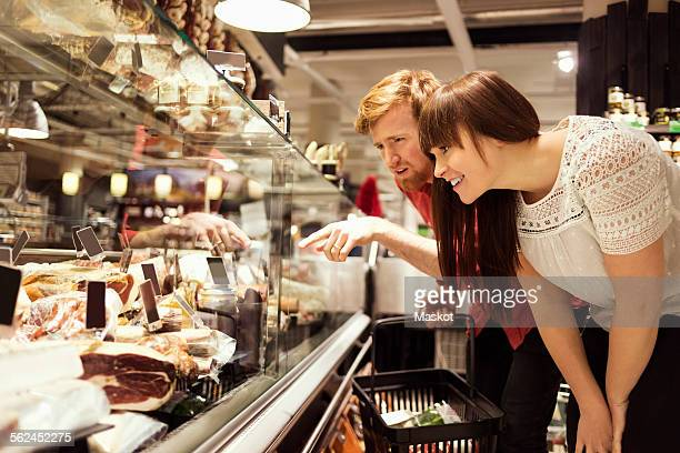 Young couple choosing fresh meat at supermarket