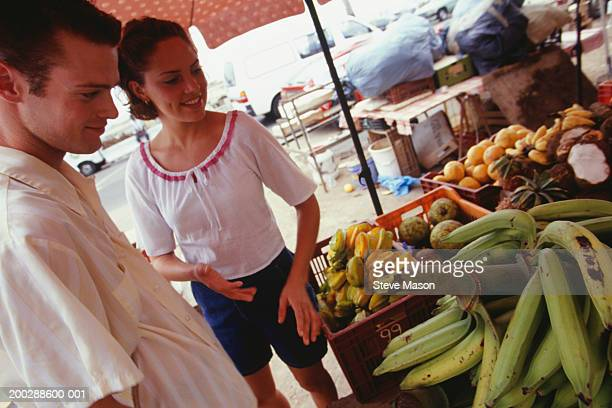 Young couple choosing fruit at outdoor market, Caribbean