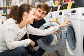 Young couple choosing washing machine in supermarket and smiling