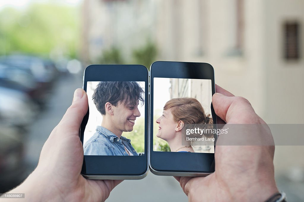 Young couple communicating via two smartphones : Stock-Foto