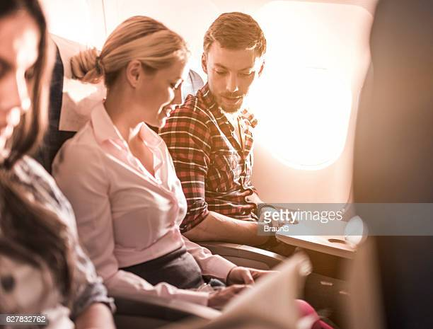Young couple communicating while traveling by airplane.