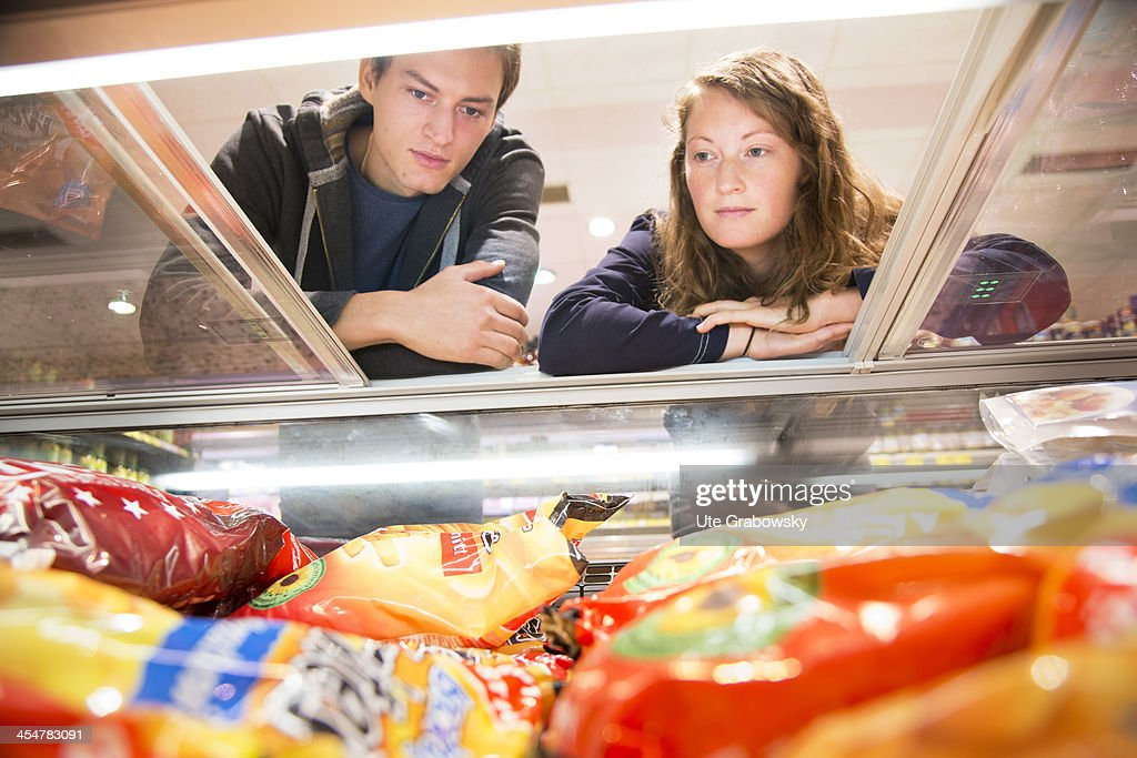 A young couple contemplating the goods at the freezer in a supermarket pictured on July 04 2013 in Bonn Germany
