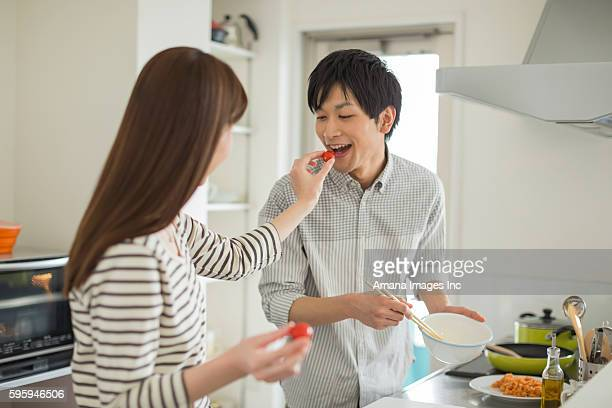 Young couple cooking and eating cherry tomatoes
