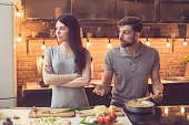 Young beautiful couple in kitchen. Family of two quarrelling while preparing food. Nice loft interior with light bulbs