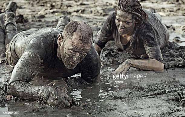 Jeune couple ramper ensemble lors d'une course dans la boue