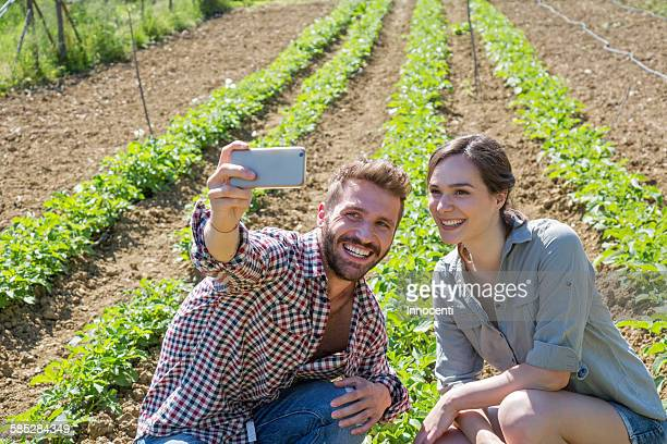 Young couple crouched in vegetable garden using smartphone to take selfie