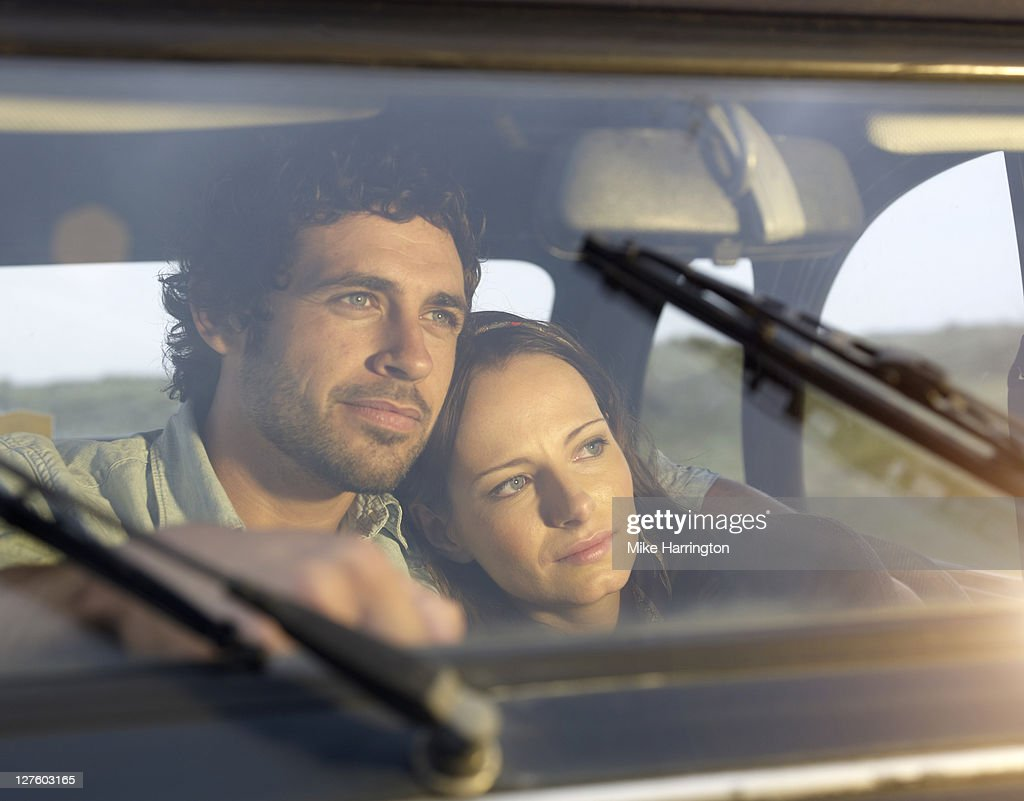 Young couple cuddling whilst gazing out of window : Stock Photo