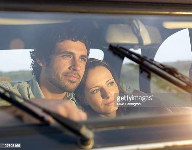 Young couple cuddling whilst gazing out of window