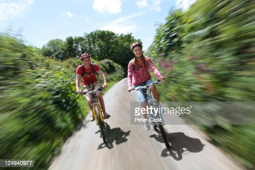 young couple cycling in country lane : Stock Photo