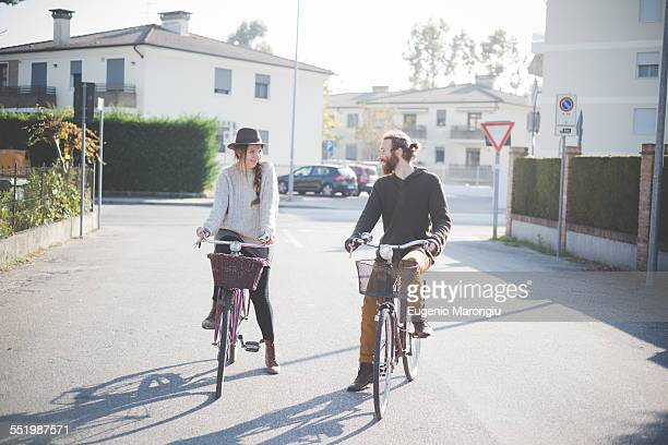 Young couple cycling on road, Dolo, Venice, ITaly